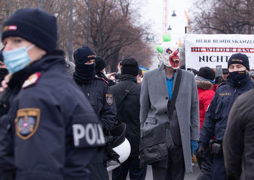 Policiais e um manifestante contra medidas restritivas para combater a COVID-19 em Viena, Áustria