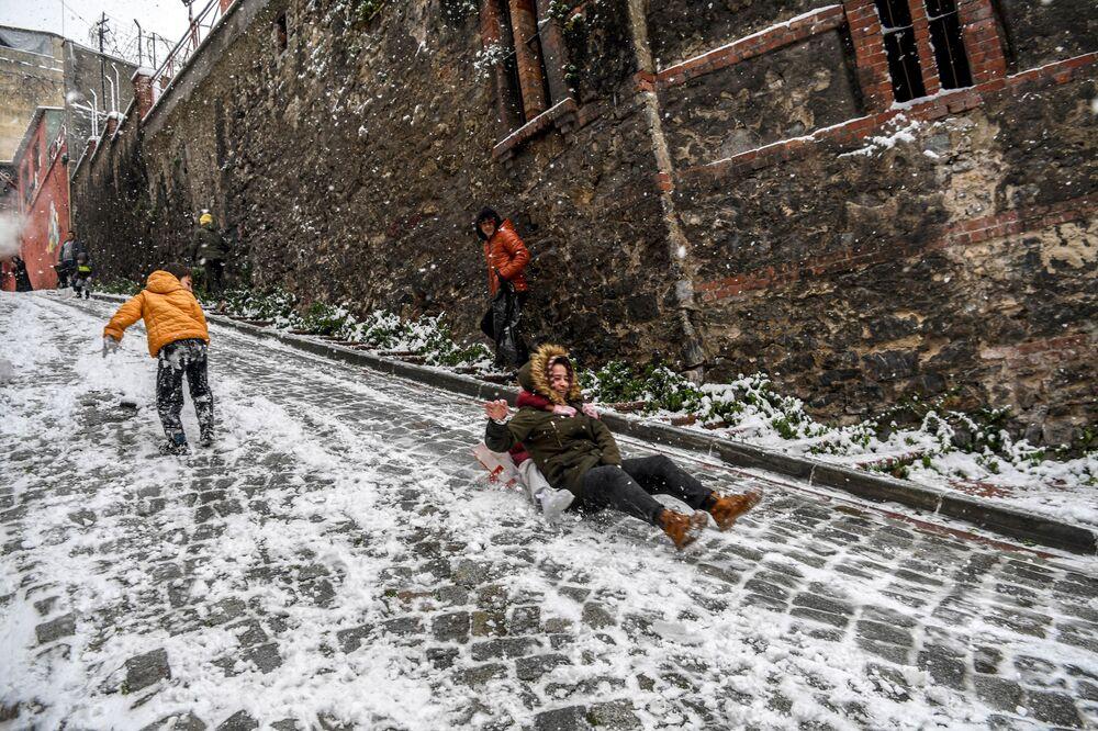 Crianças deslizam em rua coberta de neve, Istanbul, Turquia, 18 de janeiro de 2021
