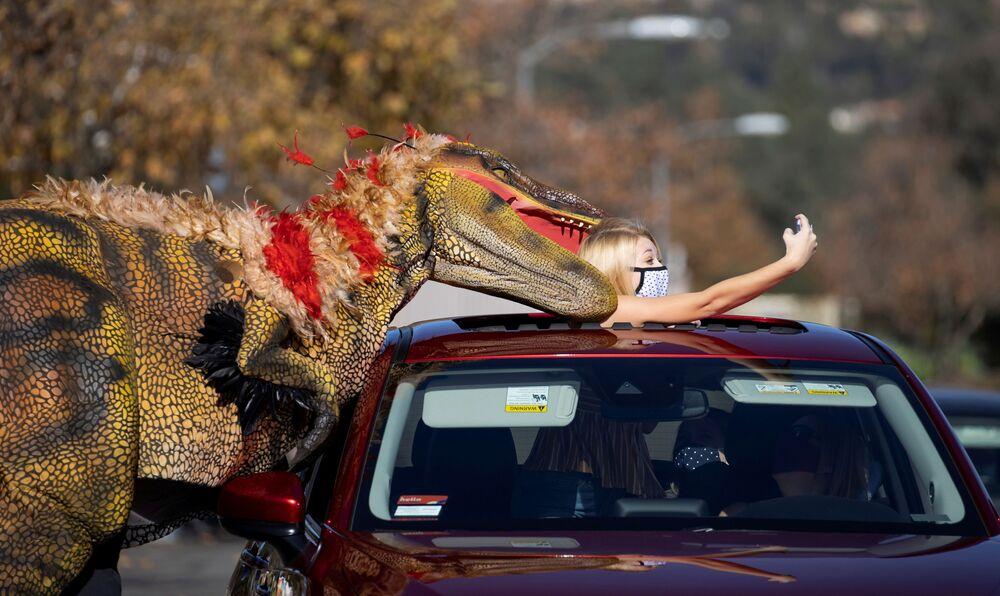 Menina tira selfie com um funcionário fantasiado de dinossauro, Califórnia, EUA, 15 de janeiro de 2021