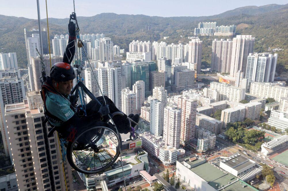 Alpinista paraplégico Lai Chi-wai tenta subir a Torre Nina de 320 metros de altura usando apenas a força do tronco, em Hong Kong, China, 16 de janeiro de 2021