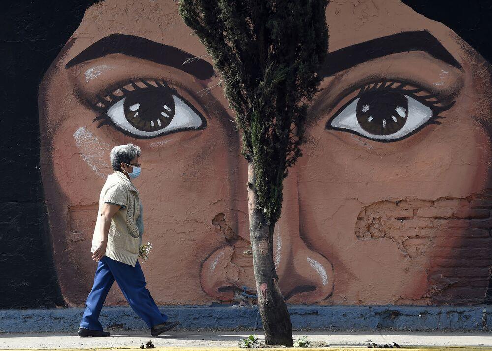 Mulher com máscara passa diante do muro do cemitério San Nicolas Tolentino na municipalidade de Iztapalapa, México, 15 de janeiro de 2021