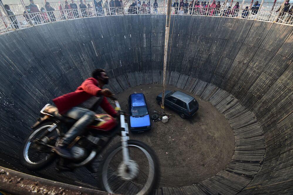 Motociclista acrobata executa acrobacia no show Wall of Death (Muro da Morte, em português) durante festival na Índia, 20 de janeiro de 2021