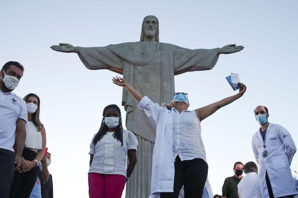 Dulcineia da Silva Lopes levanta as mãos após ter recebido a vacina Sinovac na estátua do Cristo Redentor em Rio de Janeiro, Brasil, 18 de janeiro de 2021