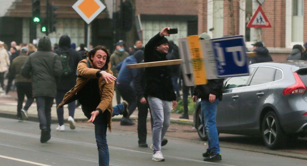 Um manifestante joga um cartaz durante um protesto contra as restrições impostas para conter a propagação da COVID-19, em Amsterdã, Países Baixos