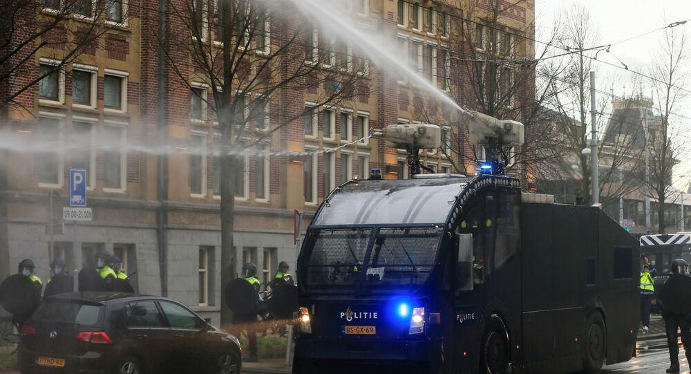A polícia usa um canhão de água durante protesto contra as restrições impostas para conter a propagação da COVID-19, em Amsterdã, Países Baixos