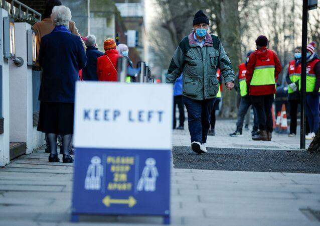 Homem usando máscara de proteção passa pela fila para vacinação contra a COVID-19, Londres, Reino Unido, 22 de janeiro de 2020
