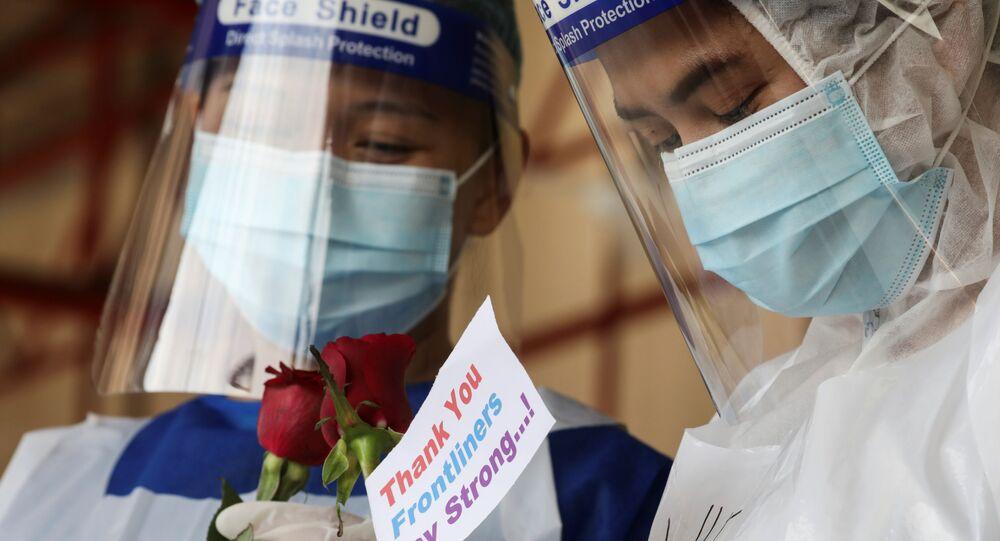 Profissionais de saúde seguram rosas oferecidas por cidadãos em um centro de testes para a COVID-19 na Malásia, 25 de janeiro de 2021