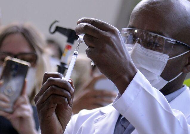 Servidor público manipula dose de vacina da Oxford/AstraZeneca contra COVID-19, em Brasília, 23 de janeiro de 2021
