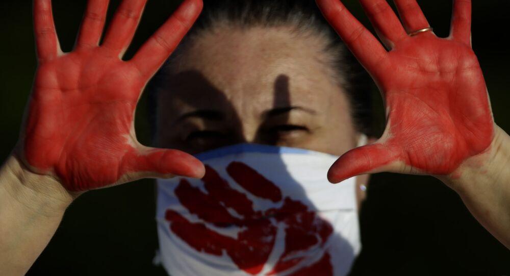 Manifestante pinta mãos de vermelho durante ato a favor do impeachment do presidente do Brasil, Jair Bolsonaro, Brasília, 24 de janeiro de 2021