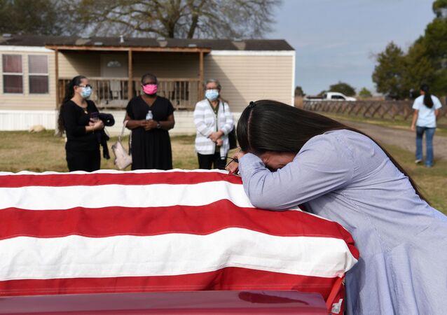 Pessoas em luto durante enterro de parente, falecido em função da COVID-19, em San Felipe, Texas, EUA, 26 de janeiro de 2021