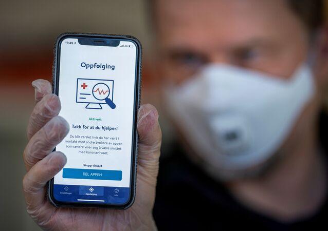 Em Oslo, na Noruega, um homem mostra na tela de um celular um aplicativo de rastreamento de casos de COVID-19 do Instituto Nacional de Saúde Pública do país, em 16 de abril de 2020