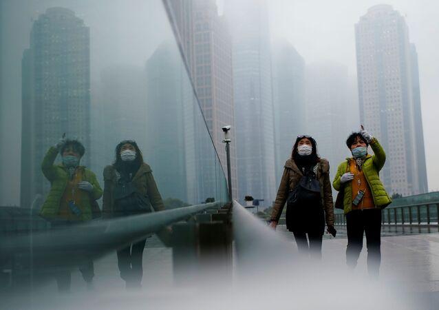 Pessoas com máscaras andam pela rua durante a pandemia, Shanghai, China, 26 de janeiro de 2021