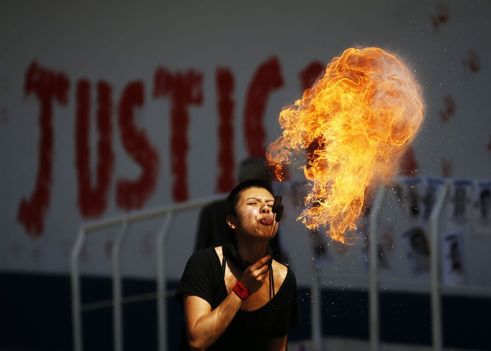 Ativista cospe bolas de fogo durante protesto em frente da Procuradoria-Geral na Cidade do México, México, 25 de janeiro de 2021