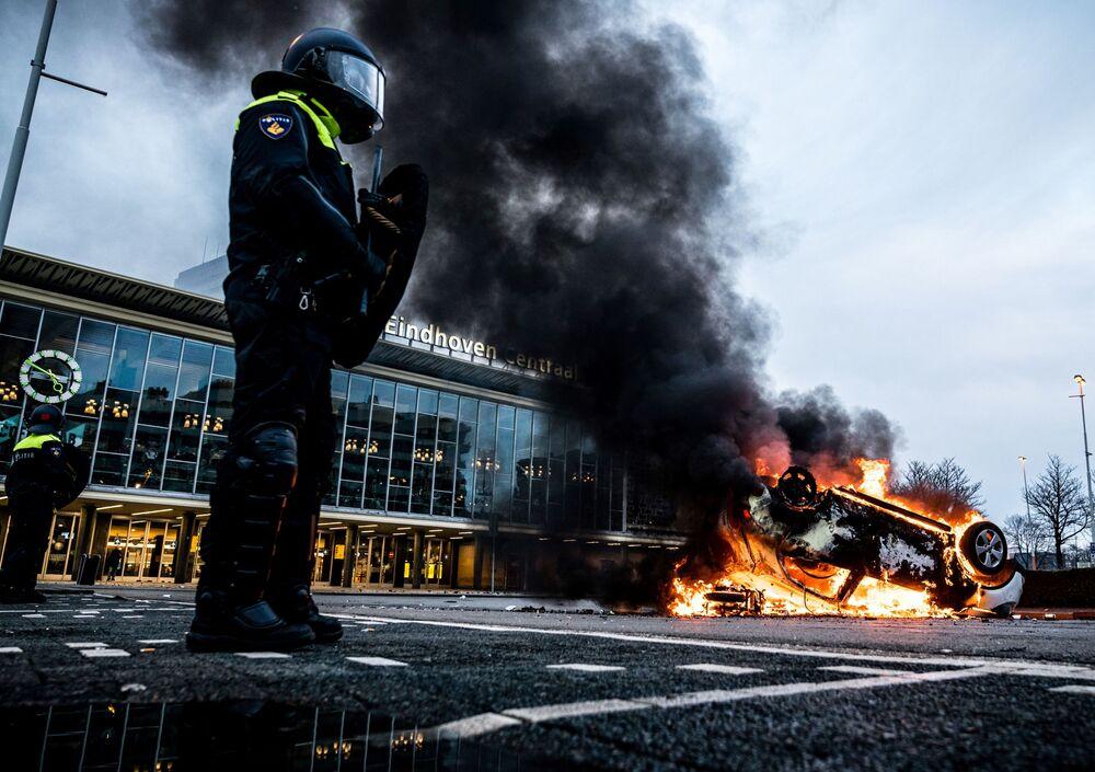 Carro em chamas em frente da estação ferroviária, 24 de janeiro de 2021, após protestos contra a política do coronavírus, em Eindhoven, Países Baixos, 24 de janeiro de 2021