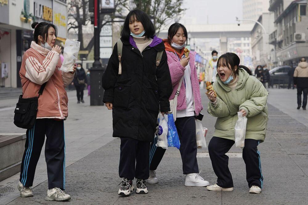 Meninas chinesas passeiam pelas ruas na província de Wuhan, China, 26 de janeiro de 2021