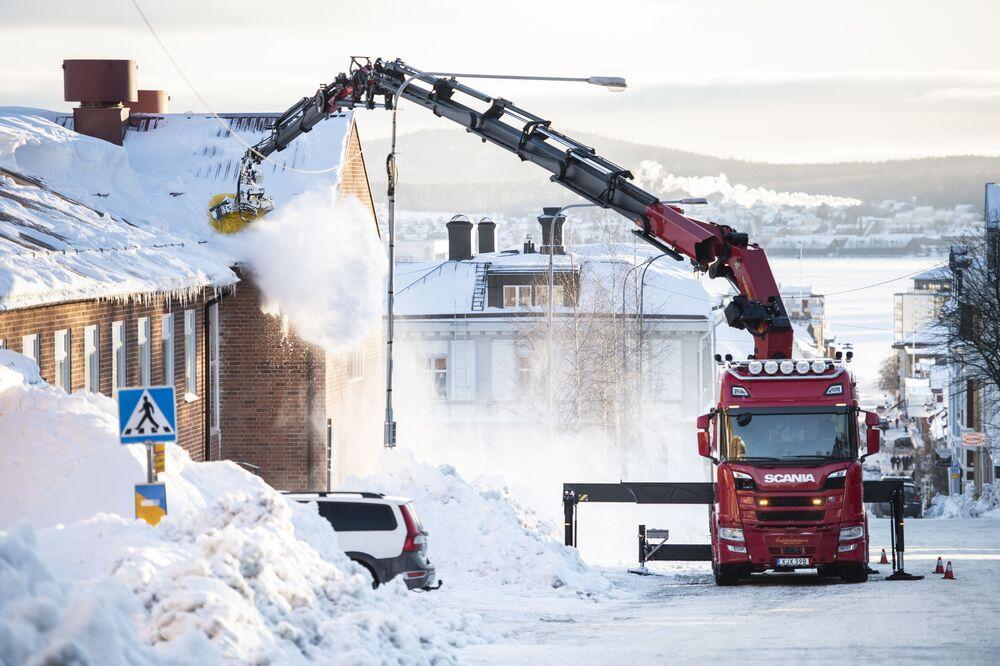 Telhado é limpo da neve no centro de Ornskoldsvik, na Suécia, em 26 de janeiro de 2021