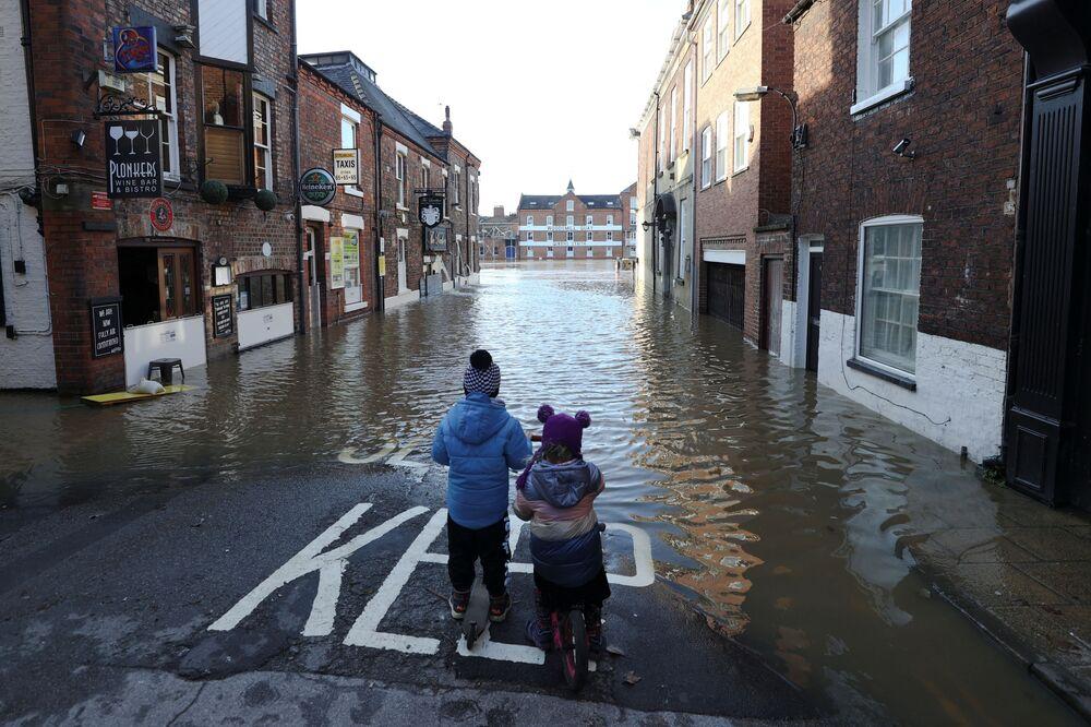 Duas crianças em rua parcialmente inundada após o rio Ouse transbordar, no Reino Unido, 22 de janeiro de 2021