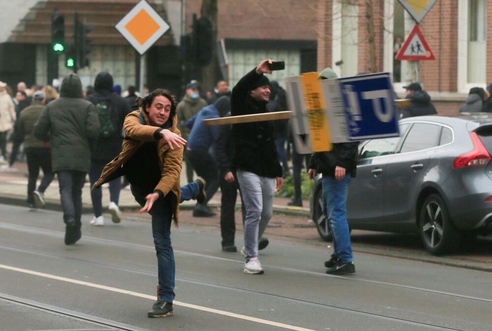 Manifestante joga placa de rua durante protesto contra restrições para conter a propagação do coronavírus, Amsterdã, Países Baixos, 24 de janeiro de 2021