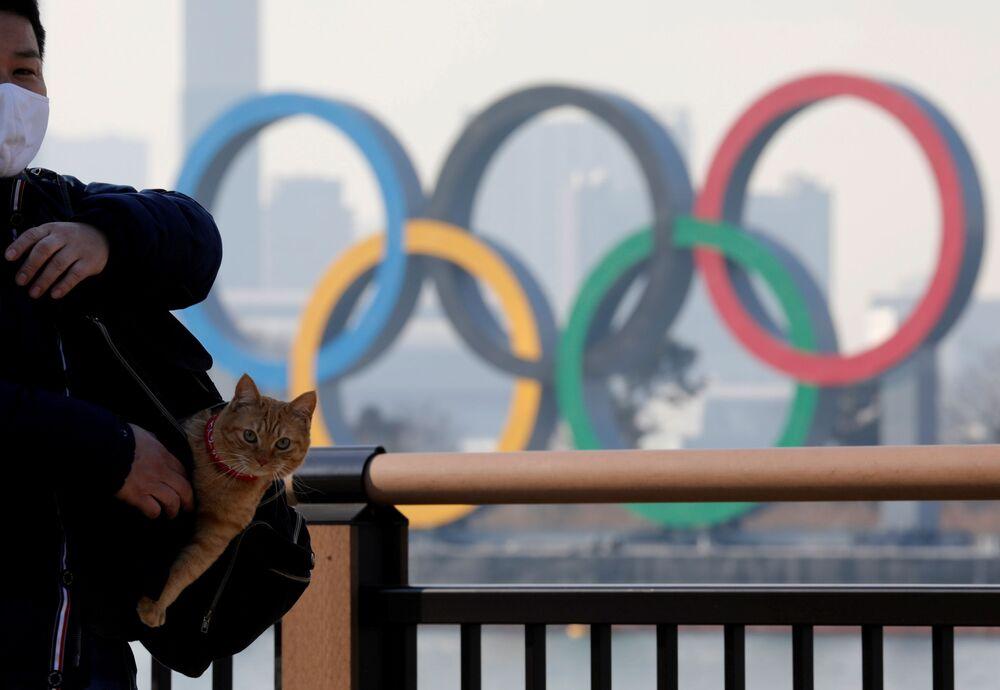 Homem com gato no saco em frente aos anéis olímpicos, Tóquio, Japão, 22 de janeiro de 2021
