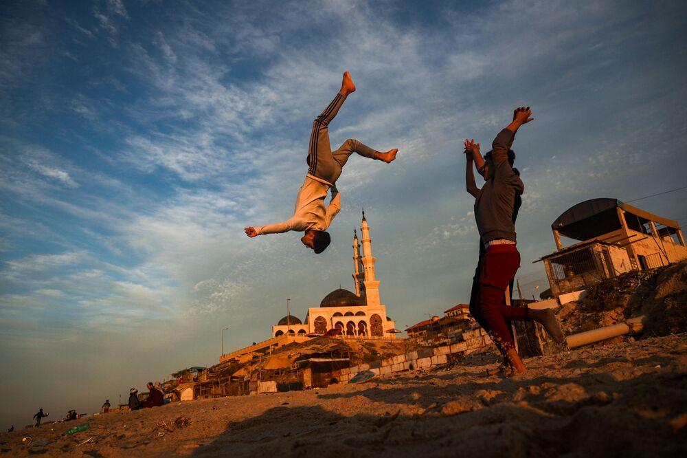 Crianças palestinas praticam parkour ao longo de uma praia na cidade de Gaza, Palestina, ao pôr do sol, em 27 de janeiro de 2021