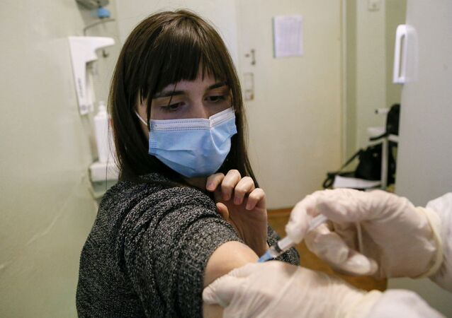 Mulher recebe dose da vacina contra a COVID-19 Sputnik V na Ucrânia