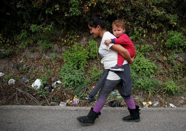 Mulher de Honduras carrega criança como parte da caravana de migrantes destinada aos EUA, em Chiquimula, Guatemala, 16 de janeiro de 2021