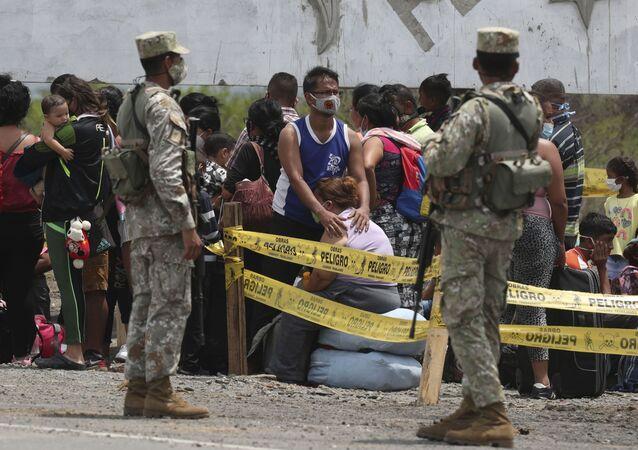Soldados peruanos guardam imigrantes venezuelanos detidos em posto fronteiriço em Tumbes, Peru (imagem referencial)
