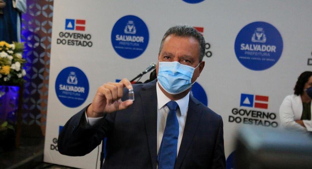 O governador da Bahia, Rui Costa, segura um frasco da vacina CoronaVac