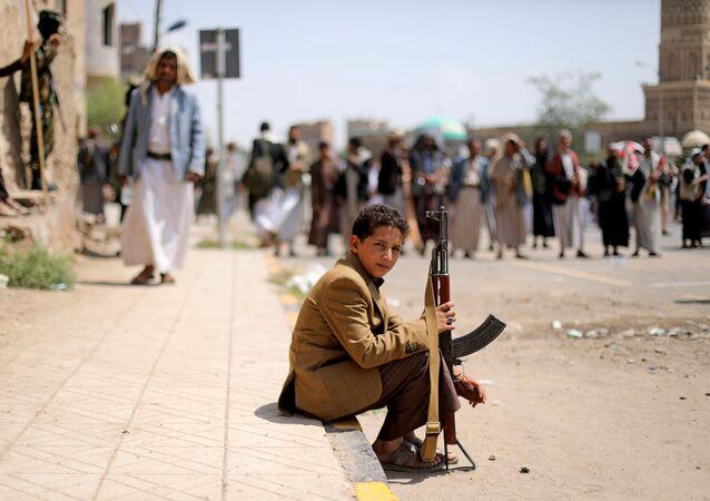 Garoto segura rifle durante ato do movimento houthi na capital do Iêmen, Sanaa, 30 de agosto de 2020 (foto de arquivo)