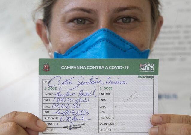 Agente da Saúde mostra seu certificado de vacinação, após receber primeira dose de imunizante contra a COVID-19, em São Paulo, 3 de fevereiro de 2021