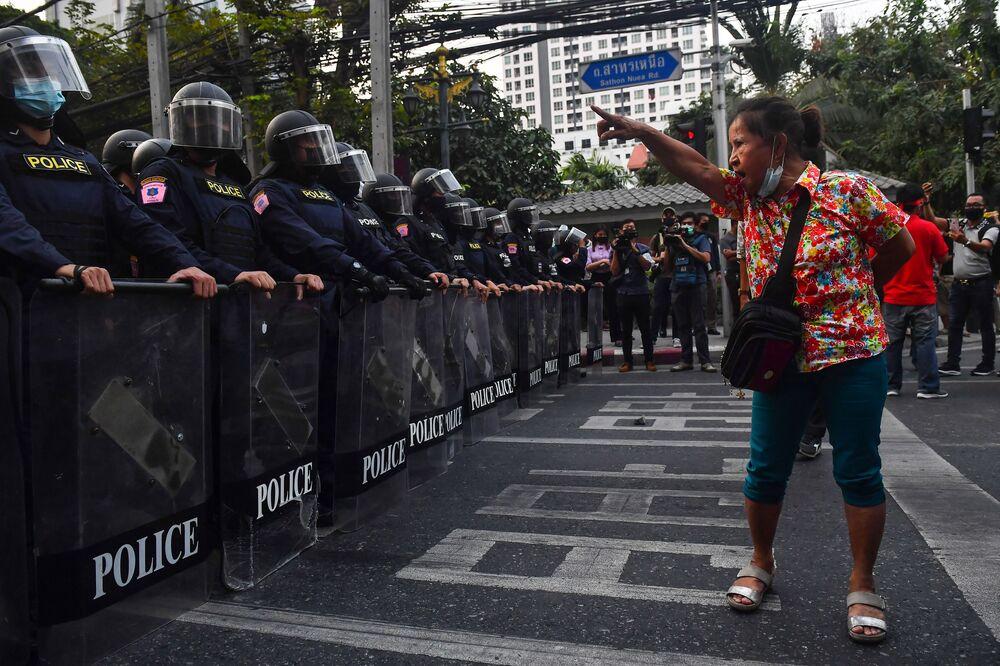Manifestante em Bangkok, Tailândia, mostra gestos à polícia de choque, em 1º de fevereiro de 2021, perto de migrantes de Mianmar protestando após o golpe militar em seu país