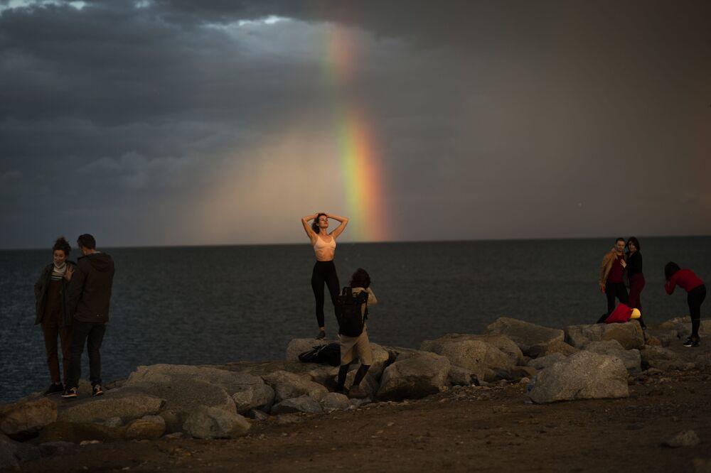 Pessoas tiram fotos em frente a arco-íris após tempestade em Barcelona, Espanha, 30 de janeiro de 2021