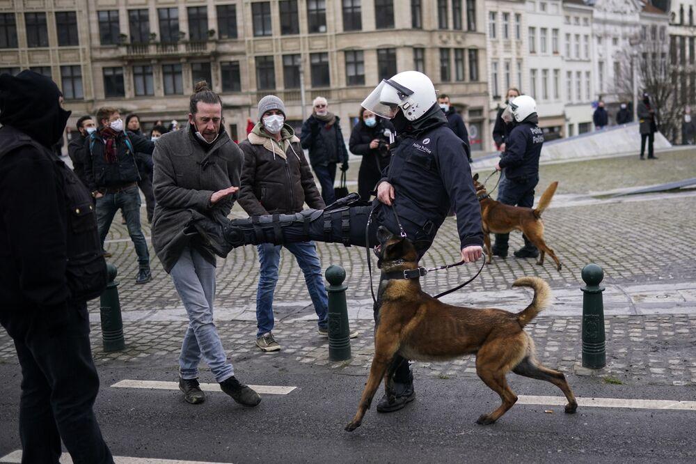 Policial pontapeia manifestante durante protesto não autorizado contra as restrições pandêmicas em Bruxelas, Bélgica, 31 de janeiro de 2021