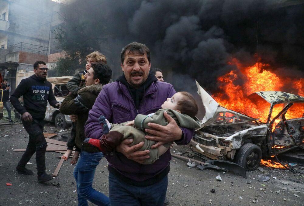 Homem leva criança ferida por explosão de um carro-bomba na cidade de Azaz, Síria, em 31 de janeiro de 2021