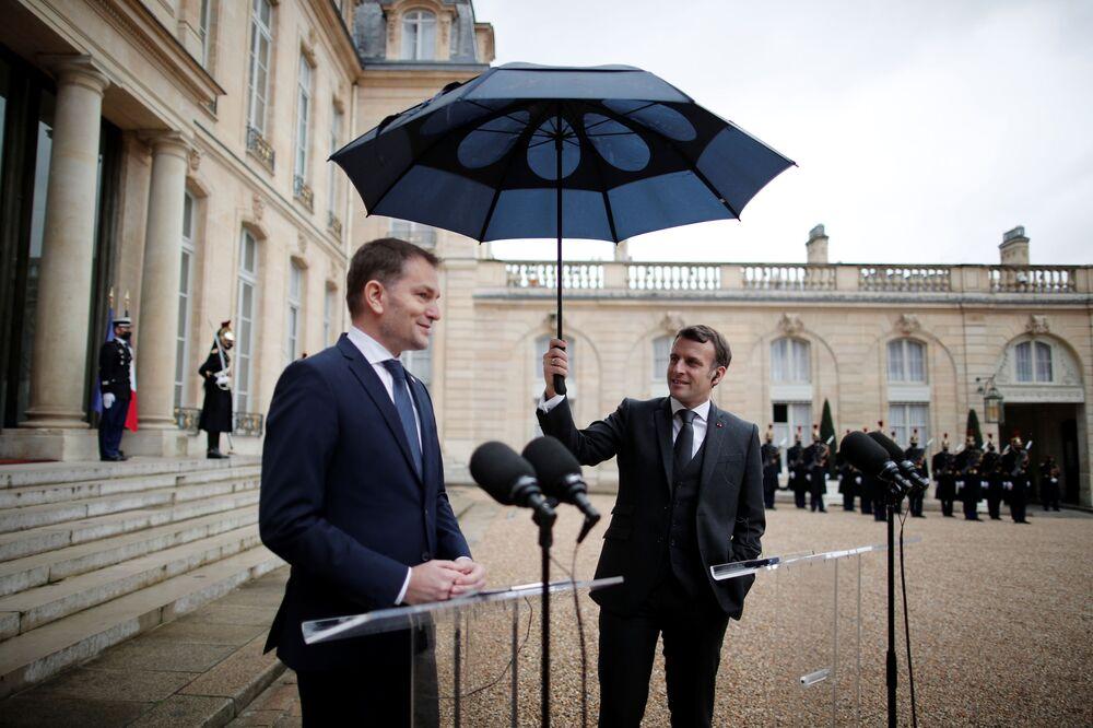 Presidente da França, Emmanuel Macron, carrega guarda-chuva ao lado do primeiro-ministro da Eslováquia, Igor Matovic, durante comunicação conjunta no Palácio do Elysée em Paris, França, 3 de fevereiro de 2021