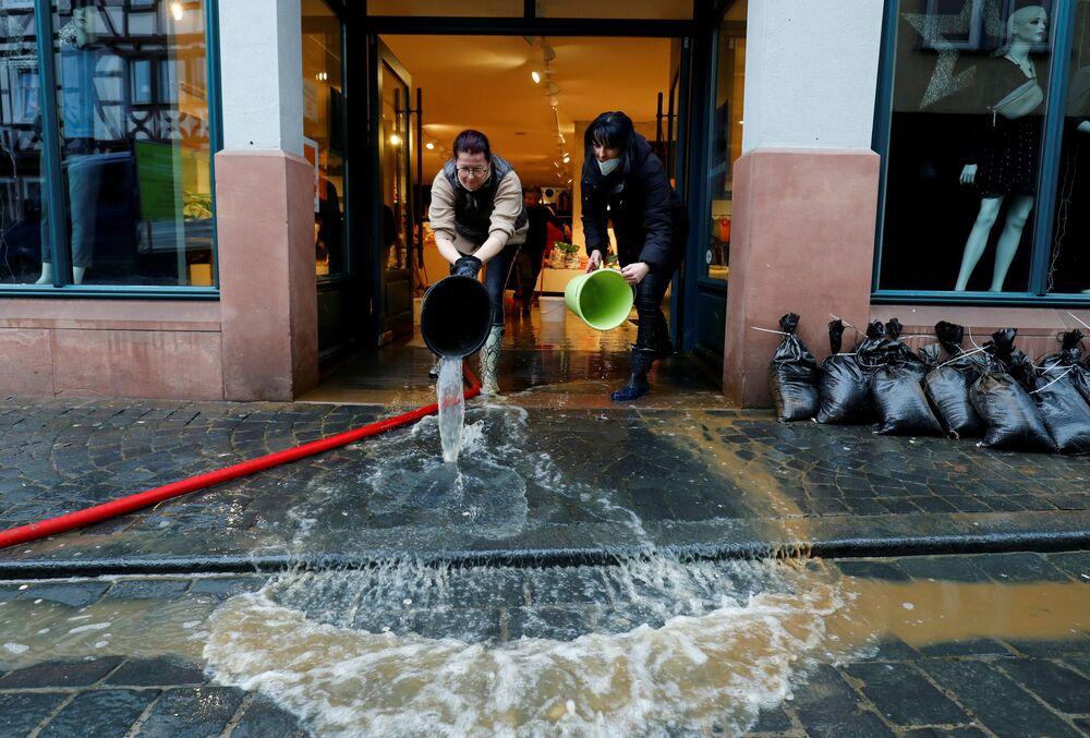 Empregadas de loja de roupa limpam consequências de inundação na cidade de Buedingen, Alemanha, 30 de janeiro de 2021