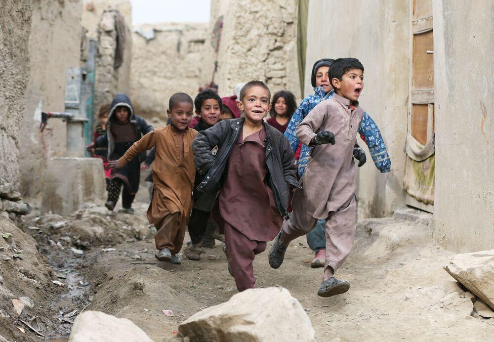Crianças afegãs brincam perto de seus abrigos nos arredores de Cabul, Afeganistão, 3 de fevereiro de 2021