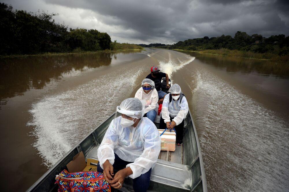 Profissionais da saúde municipais vão de barco ao longo das margens bancos do rio Solimões, onde vivem Ribeirinhos, para fornecer a vacina AstraZeneca/Oxford contra o coronavírus, Manacapuru, Brasil, 1º de fevereiro de 2021