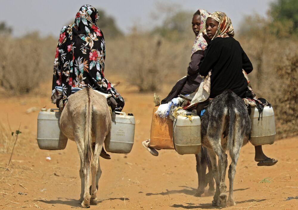 Mulheres sudanesas transportam água em burro no povoado de al-Taweel Saadun, Sudão, 2 de fevereiro de 2021