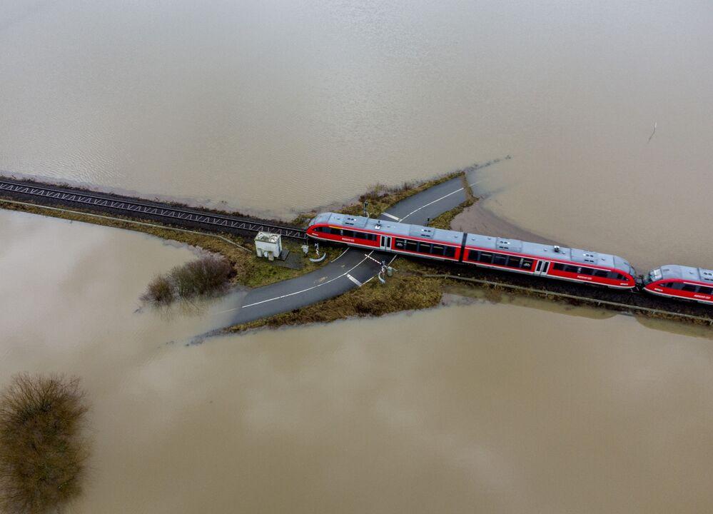 Trem passa cruzamento de ferrovia rodeado por água devido a inundação causada pela chuva e degelo, Alemanha, 3 de fevereiro de 2021