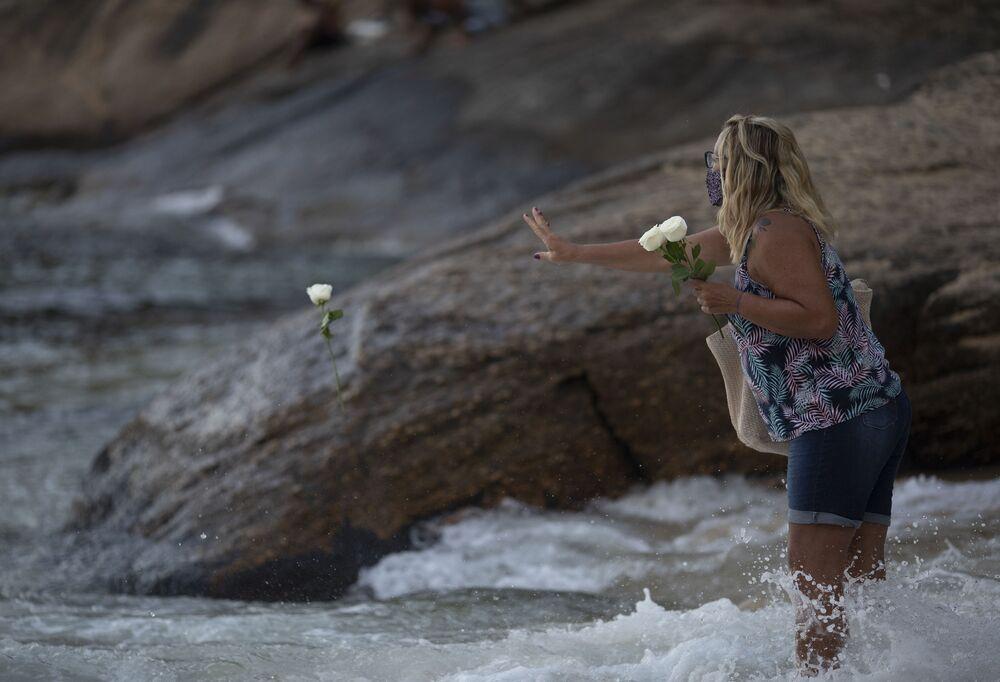 Mulher joga flores no oceano como oferenda à deusa do mar Iemanjá, no culto de matriz africana, na Praia Vermelha, Rio de Janeiro, 2 de fevereiro de 2021