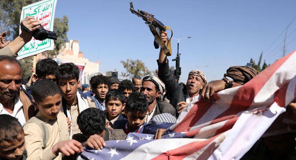 Apoiadores dos rebeldes houthis rasgam bandeira americana durante protesto em Sanaa