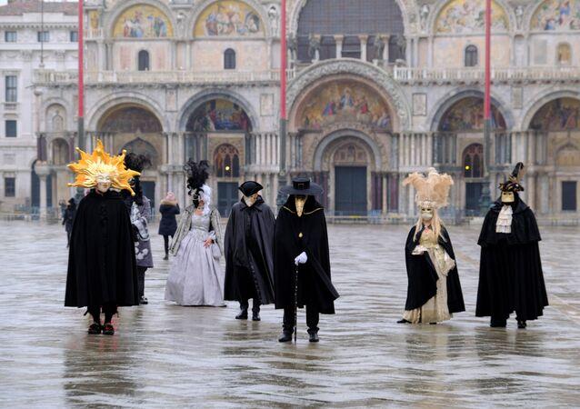 Com distanciamento social, pessoas de máscaras e fantasias celebrar o que seria o início do carnaval de Veneza, cancelado por conta da pandemia de COVID-19, no dia 7 de fevereiro de 2021