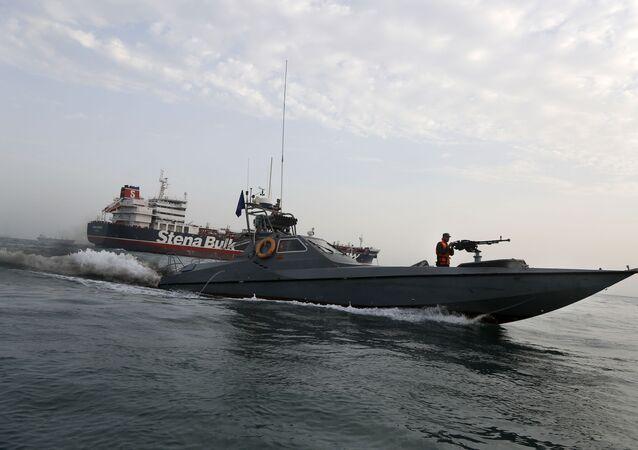Lancha do Corpo de Guardiões da Revolução Islâmica passa junto do petroleiro Stena Impero, com bandeira do Reino Unido, no porto de Bandar Abbas, Irã, 21 de julho de 2019