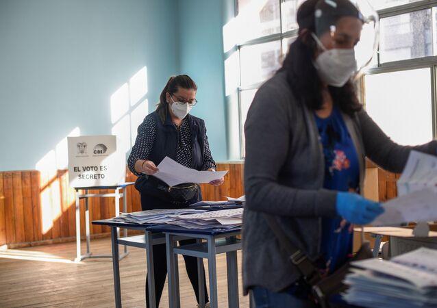 Mulheres trabalham em processo de apuração dos votos das eleições presidenciais do Equador.