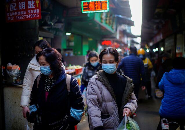 Pessoas usando máscaras de proteção em um mercado de rua durante o surto da COVID-19, Wuhan, China, 8 de fevereiro de 2021