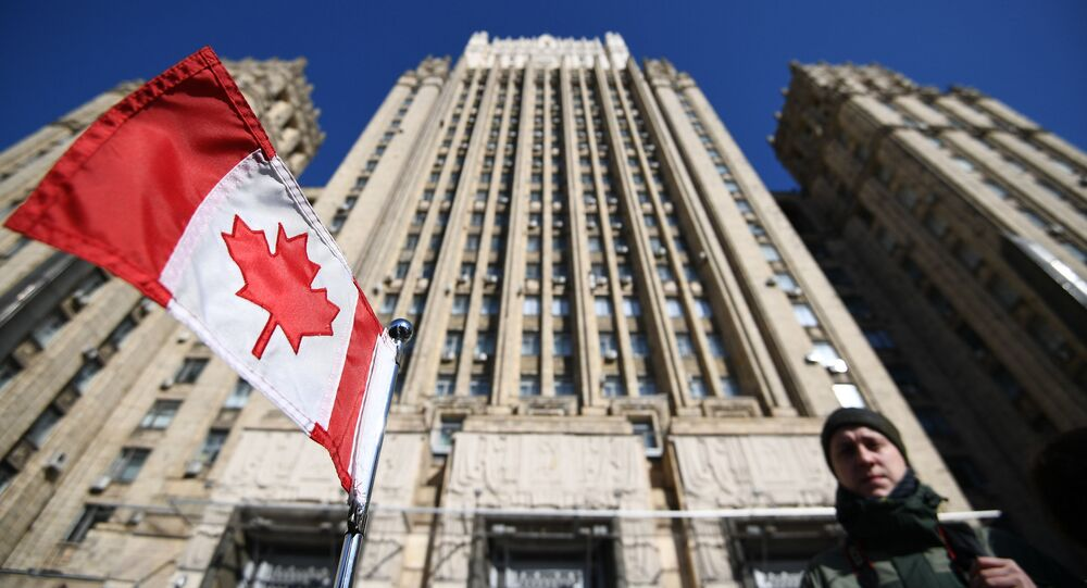 Bandeira nacional do Canadá no carro da embaixada canadense em frente ao prédio do Ministério das Relações Exteriores da Federação da Rússia, para onde foram convocados embaixadores de países que expulsaram diplomatas russos