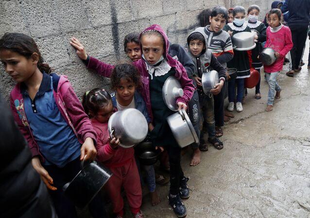 Crianças palestinas fazem fila para receberem refeição de graça em na cidade de Gaza, Palestina, 4 de fevereiro de 2021