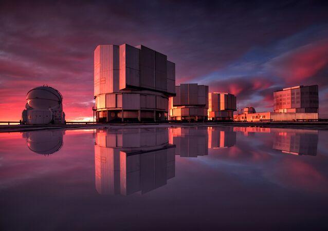 The Very Large Telescope, ou o Telescópio VLT, no Observatório do Paranal no deserto do Atacama, no Chile. A instrumentação do VLT foi adaptada para conduzir uma busca por planetas no sistema Alpha Centauri. Esta imagem do VLT é pintada com as cores do pôr do sol refletido na água da plataforma