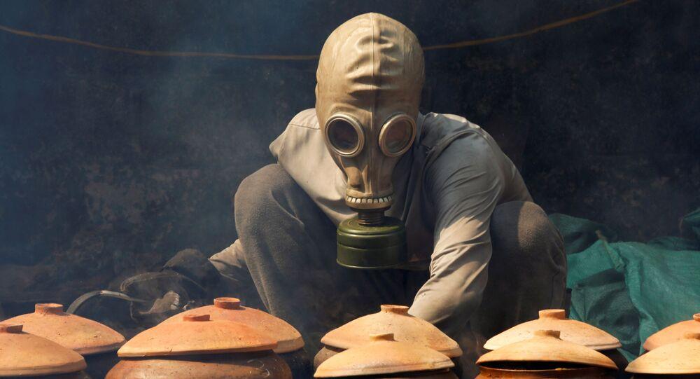Homem usa máscara protetora enquanto prepara refeições típicas do Ano Novo Lunar, em Ha Na, Vietnã, 5 de fevereiro de 2021
